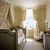 Bedroom in a traditional English country home - curtain, canopy and wallpaper with the same color and design