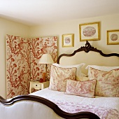 An antique double bed with a padded headboard and gold framed pictures