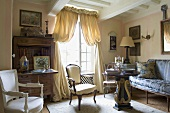 A classic country style living room with antique seats and a window with a gathered curtain