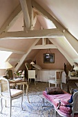 A bedroom in a rustic converted attic with wooden beams, antique chairs and a chaise longue