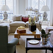 A modern wooden coffee table and a light, upholstered sofa in front of floor-to-ceiling windows