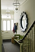 A hallway in a country-house with a mirror framed in a steering wheel and a green wooden bank