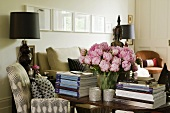 A bunch of pink peonies between two stacks of books on a table and a table lamp with a black shade next to upholstered armchair