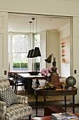 Antiker Holztisch und gemusterter Sessel vor Durchgang ins Esszimmer mit Blick auf Tisch und Stühlen