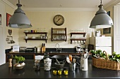 An open-plan kitchen in a country house - metal lamps hanging above a black work surface with kitchen utensils and a plate rack hanging on the wall