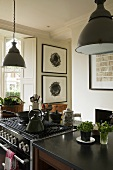 Metal lampshades above a kitchen counter and a cooker in an open plan kitchen in a country house
