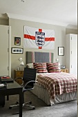 A boy's room with the English national flag hanging above the bed and a black swivel chair in front of a desk