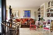 A living room with old wooden chairs and a colourful dining corner against a shelf wall and rustic floor boards