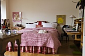 A bedroom with a pink throw on a double bed and a davenport against a wall
