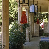 A terrace with stone pillar and lanterns with coloured tasssels hanging from the ceiling