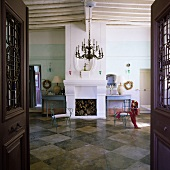 A view through an open door into a spacious living room with a chimney in a Mediterranean house and blue metal chairs on a black and white tiled floor