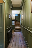 Green wood panelling in a hallway and an old wooden stairway