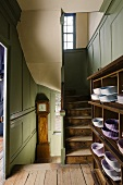 An old stairwell with a green wood panelled wall and an open cupboard on the landing filled with shirts