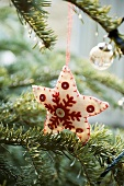 A star-shaped Christmas tree decoration made of white felt hanging from a branch