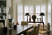 A dining table in front of an elegant occasional table set with table lamps in a bay window with closed shutters