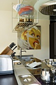 Kitchen utensils on a kitchen work surface with a stainless steel surface and a metal shelf hanging from the ceiling