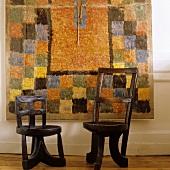 Afrikanische Holzstühle vor modernen Wandteppich