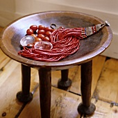 A red coral necklace on an African occasional table