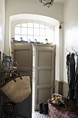 A grey front door with fanlight seen from the hallway with coat hooks on the wall