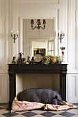 A living room in a country house - a black house pig sleeping in front of a fireplace
