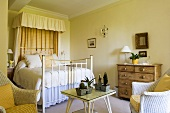 A country house-style bedroom with yellow walls and a white brass bedstead with a canopy