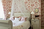 A white wooden country house-style bed with pillows, curtains and matching wallpaper