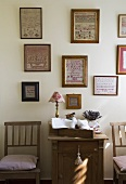 A collection of pictures on the wall above a wooden cupboard and a chair in country-house style