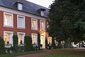 Landhaus mit weissen Fenstern und Ziegelfassade in Abendstimmung