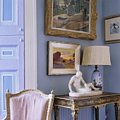 A sculpture and a table lamp with a white shade on an antique wall table and pictures hanging on a lilac-painted wall