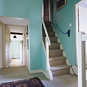 A simple stairway with turquoise-coloured walls and a grey carpet on the floor and stairs with a view of a hallway
