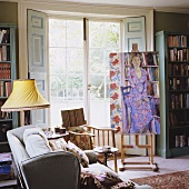 Living room in a country house with easel and picture in front of French doors with