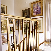 A view through a wooden banister in a stairway with pictures on the wall
