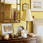 A table lamp with a white shade on a bedside table and a mirror above it on a yellow wall
