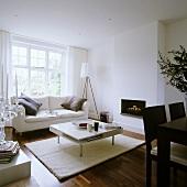Weisser Wohnraum im Designerstil mit Sofa vor Fensterfront und Couchtisch vor Kamin