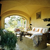 Comfortable wicker furniture with white upholstery in a yellow-painted loggia with a view of the garden