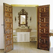 Open carved wooden doors with a view of a stone basin with a mirror in a gold frame