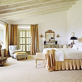 A Mediterranean-style bedroom with a carpeted floor, a double bed and a comfortable armchair under a rustic wooden beam