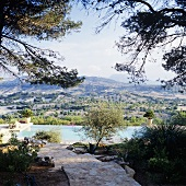 A natural stone path in a Mediterranean garden with a pool and an impressive view of the Spanish landscape
