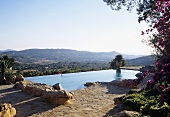 Natural stone flooring and boulders by a pool with a view of the Spanish landscape