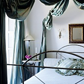 A table lamp with a white shade on a bedside table and an antique metal bed under an elegantly draped canopy