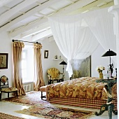 A white canopy hanging above a bed from a wood beam ceiling and antique country house-style chairs next to a window