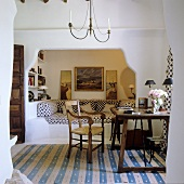 A chair and a desk on a striped rug in front of a Mediterranean-style alcove