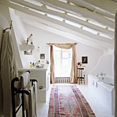 Mediterranean bath under a ceiling with wooden beams painted white and carpet runner in front of a window with curtains draped like a shawl