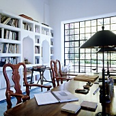 Wooden chairs at a desk in front of a concrete shelf with Moorish arches and a window with a view