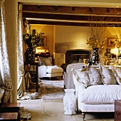 Warm artificial lighting in a country-style living room with a white sofa under a rustic wooden beamed ceiling