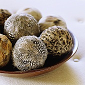 Brown and white patterned feathers on decorative balls in a wooden bowl
