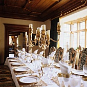 A festively laid table with silver candle sticks in the dining room of a country house
