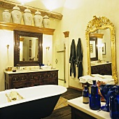 A bathroom in a country house with a free standing bathtub in front of a wash basin with a wooden cupboard and a wall mirror with a golden frame