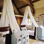 Single beds with white canopies and architectural models in a rustic bedroom