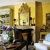 A yellow-painted living room with a fireplace and a chimney breast with a framed picture above the mantelpiece